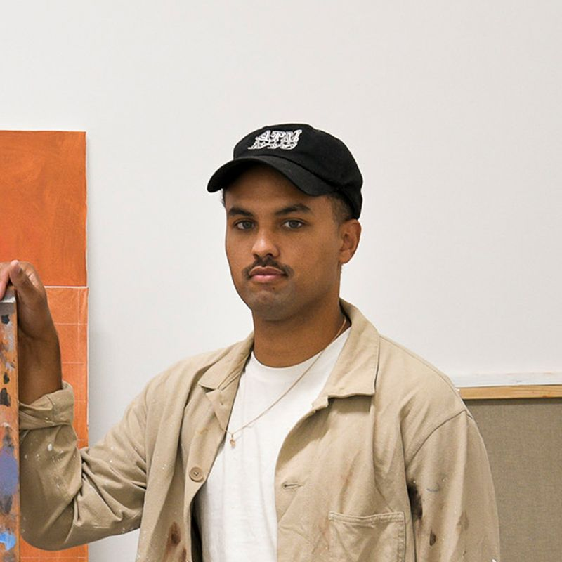 headshot of artist wearing white t-shirt, beige jacket and a black cap as he rests his hands on an easel in his studio