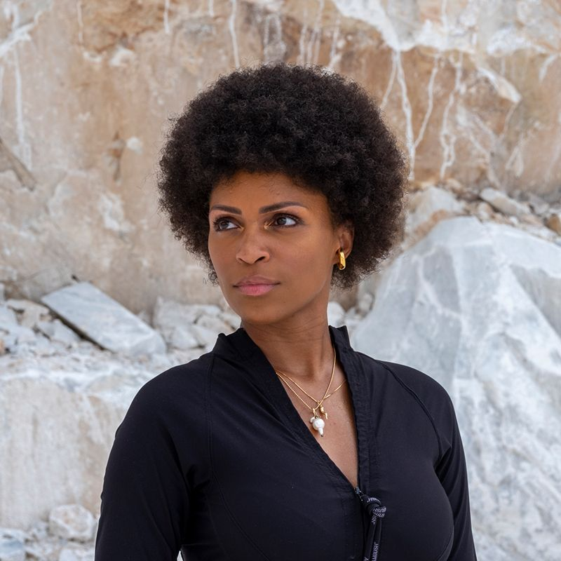 Artist wearing a black top with jewellery staring away from the camera in front of rock