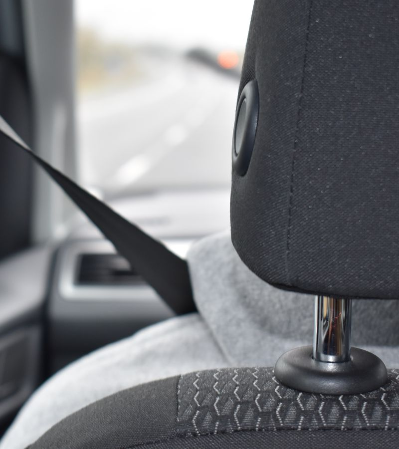 A person driving a car, the seat belt is in focus