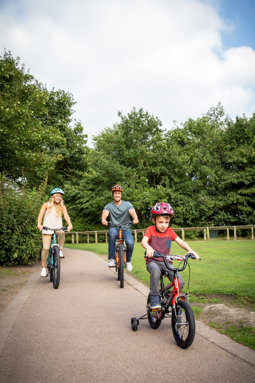Parents riding bikes behind their kid