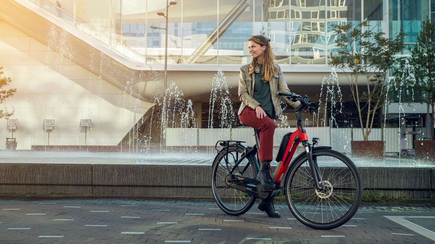 Vrouw op e-bike D-Rule van Sparta voor fontein in de stad