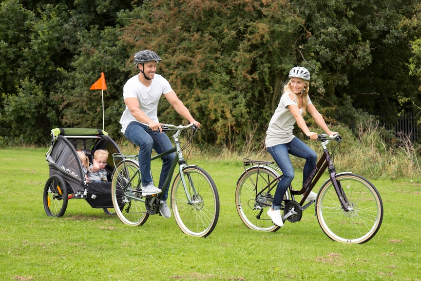 Two adults on a bike with a bike trailer and kids