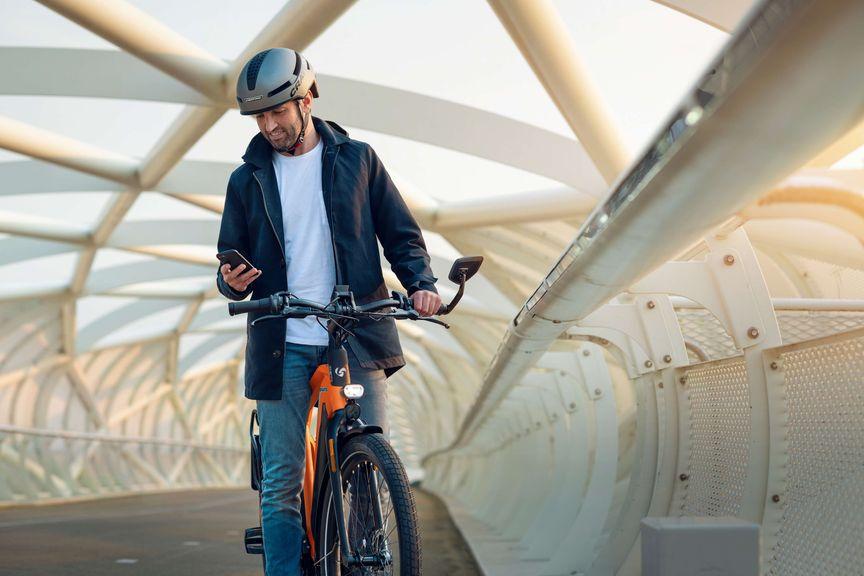Man met telefoon en helm op oranje speed pedelec van Sparta