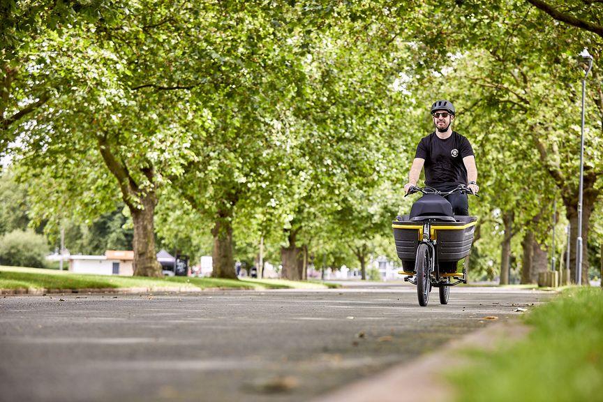 Man riding Stride 2 electric cargo bike
