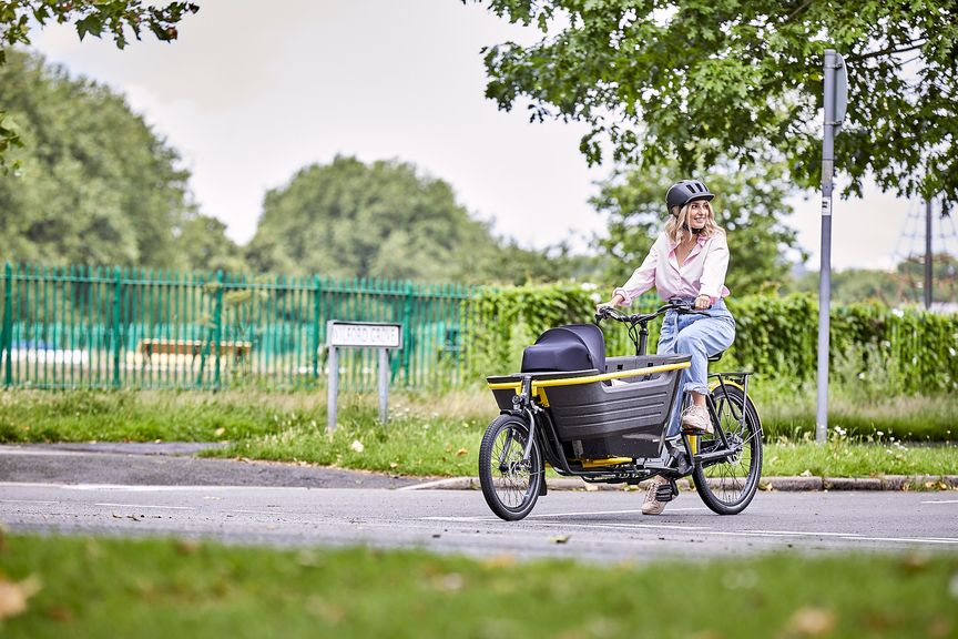 Woman standing next to Stride 2 electric cargo bike