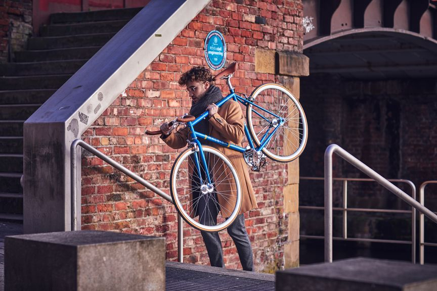 Man carrying a bike up some stairs