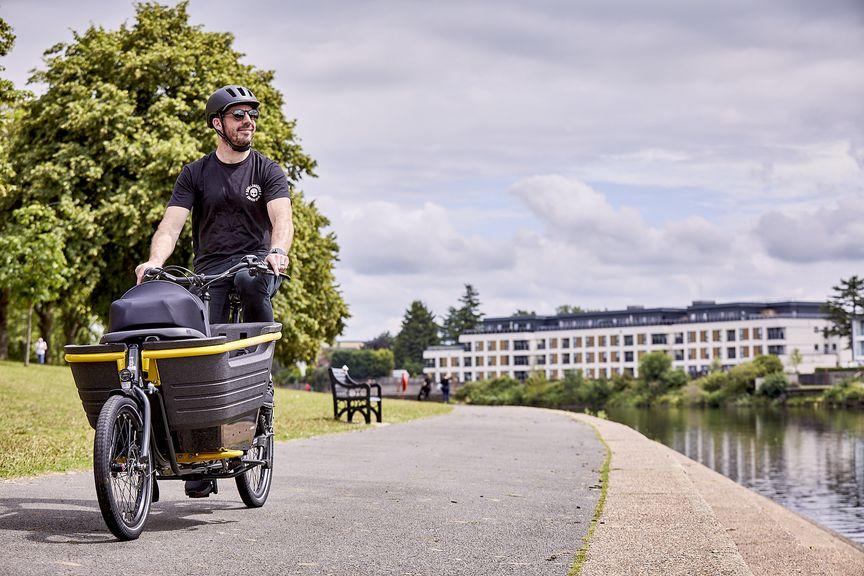 Man riding Raleigh Stride 2 electric cargo bike near river