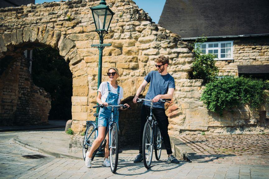 Man and woman standing next to their bikes