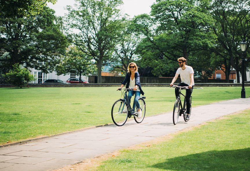 Man and woman biking through a park