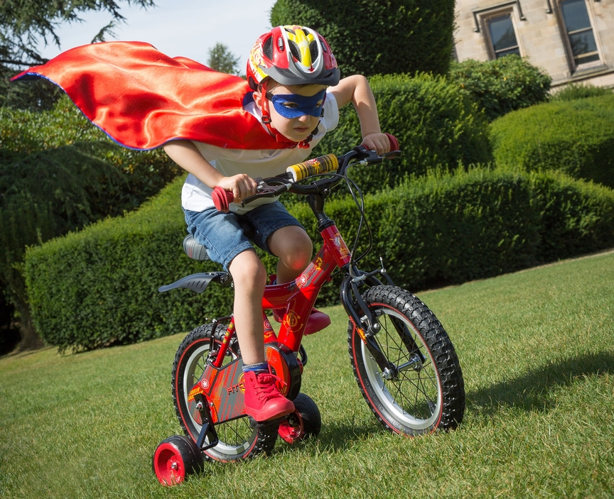 Kid on a bike with a superhero cape pretending to fly