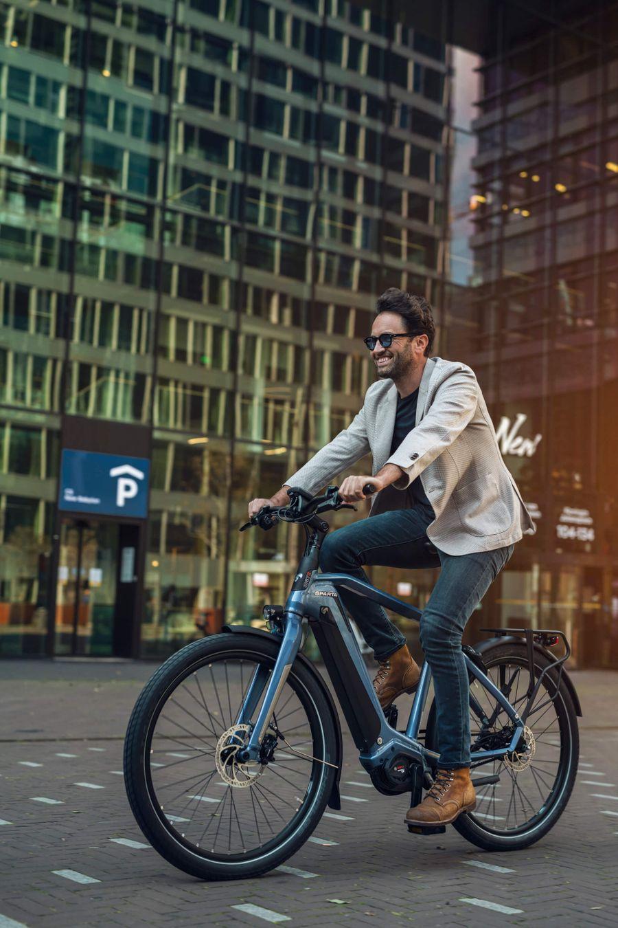 Man op blauwe Sparta e-bike voor gebouw