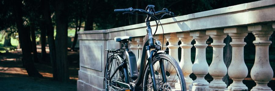 Picture showing an electric bike resting on a rock bridge fence