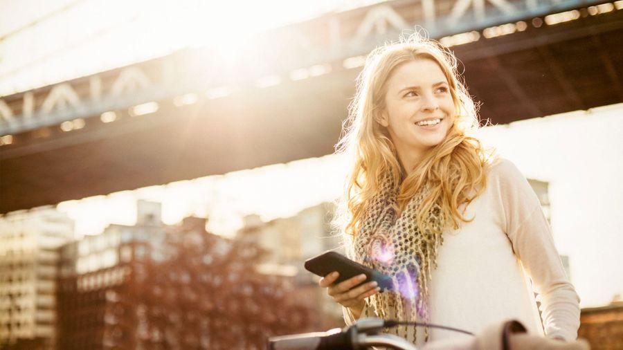 Vrouw belt bij brug op e-bike