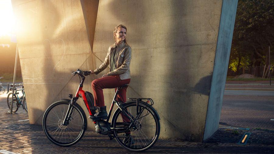 Vrouw op e-bike D-Rule van Sparta voor muur