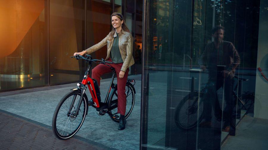 Vrouw op e-bike D-Rule van Sparta naast kantoor
