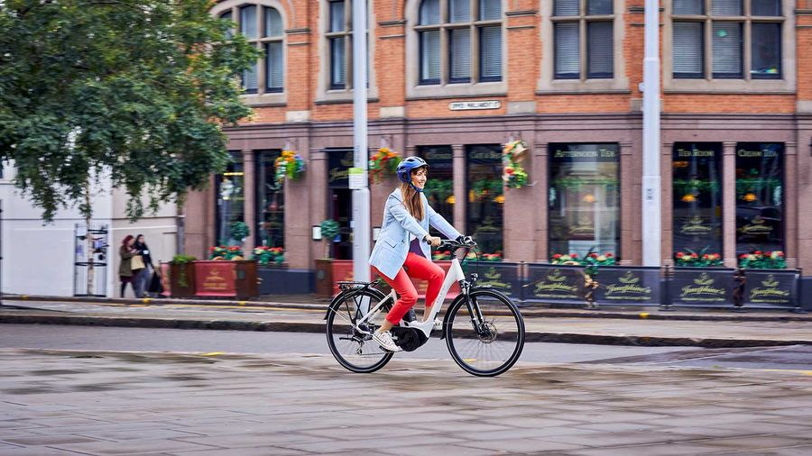 A lady riding the Raleigh Motus ebike through the city