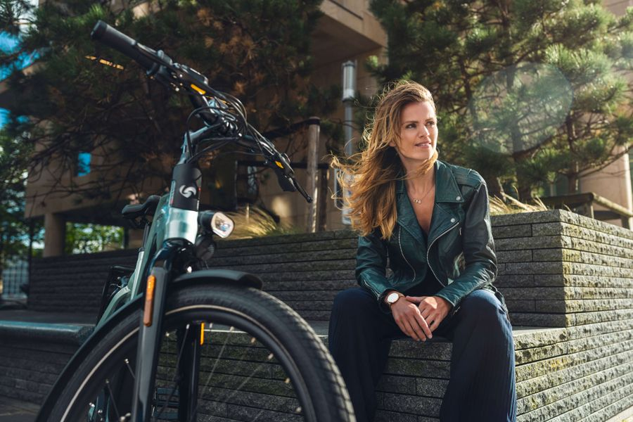 Vrouw zittend op muur met e-bike D-Burst van Sparta