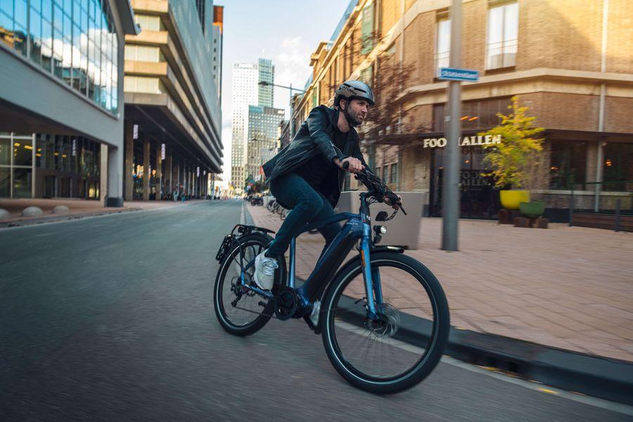Man met helm op e-bike rijdt in bocht in de stad