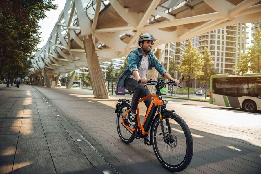 Man fietst op oranje speed pedelec van Sparta in de stad