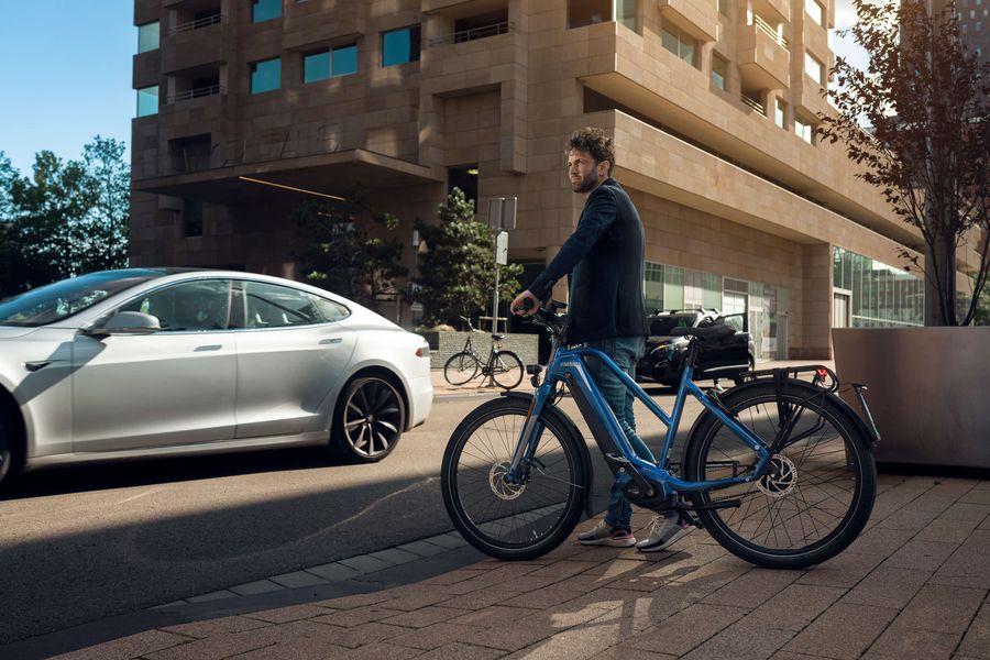 Man op e-bike D-Burst voor auto in drukke stad