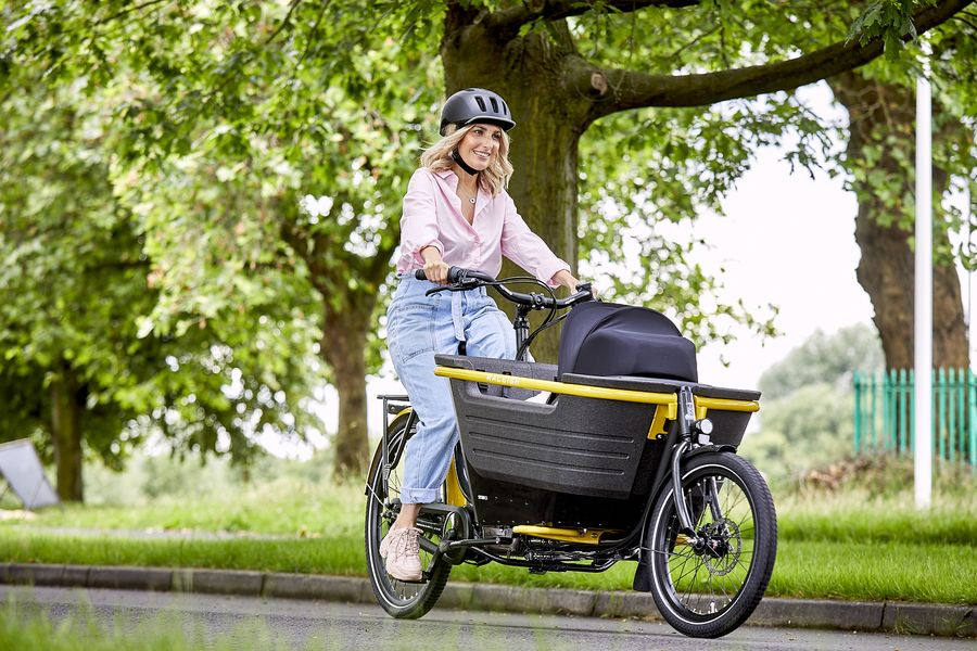 Blonde woman riding a Raleigh Stride 2 Electric Cargo Bike