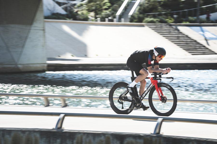 Road cyclist biking on the Lapierre time-trial Aerostorm DRS bike across a bridge