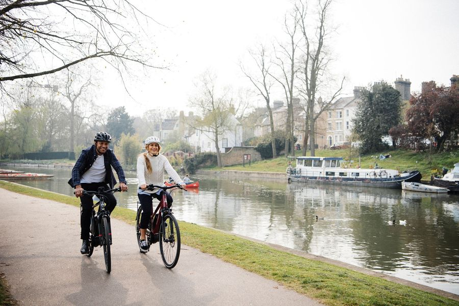 Two people biking next to a canal
