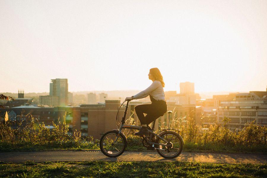 Woman biking with a sunset