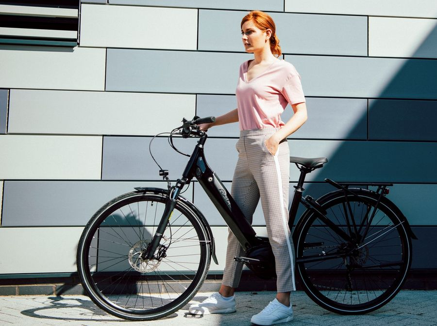 Picture of a woman standing with a Raleigh electric bike