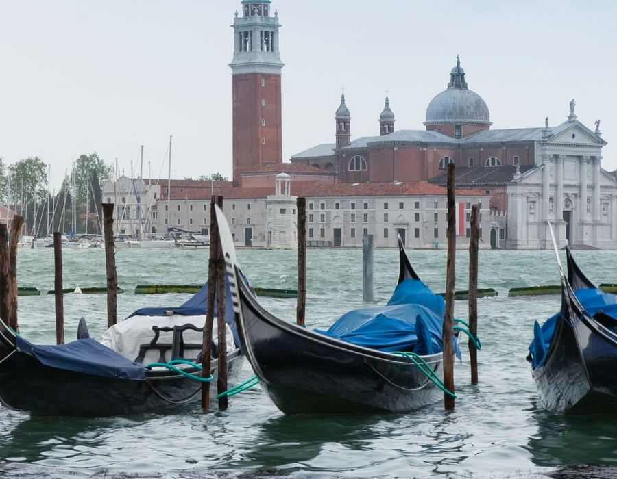 gondalas docked up along canal in venice italy