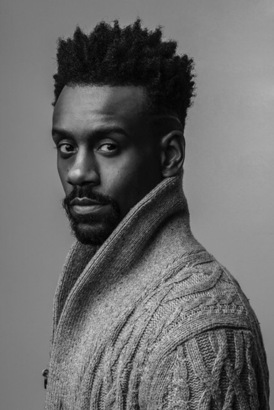 A black and white image of Kirvin in a cardigan.