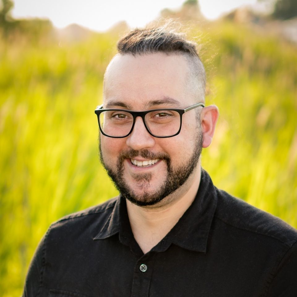 A picture of Adam smiling in a black button-up and black glasses with lush grass in the background.
