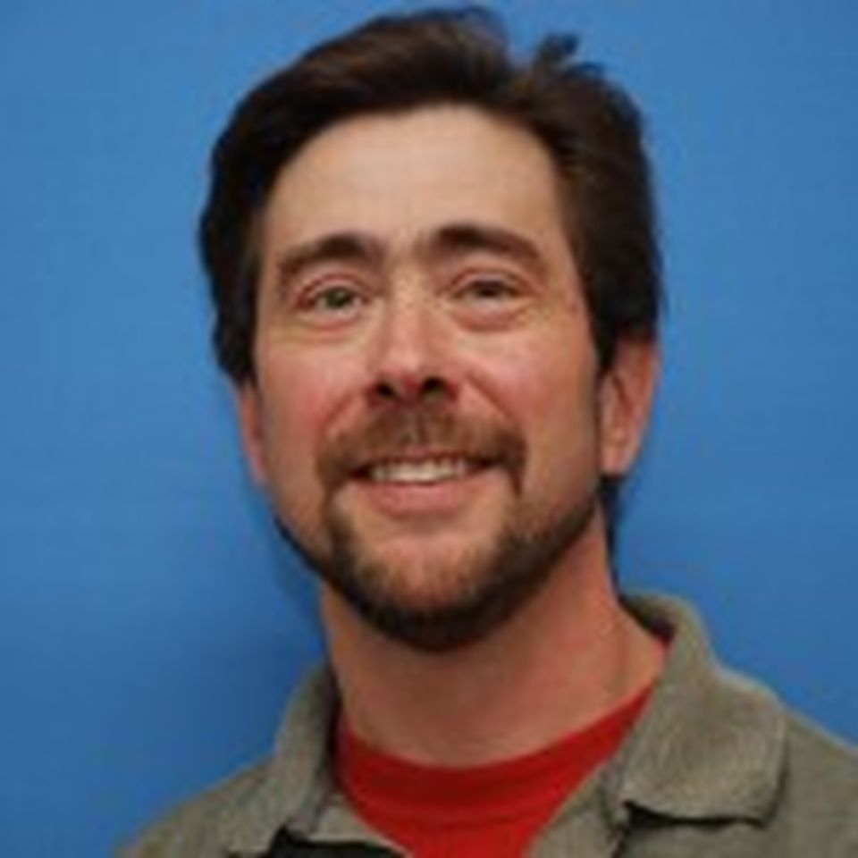 A headshot of Greg smiling against a blue background.