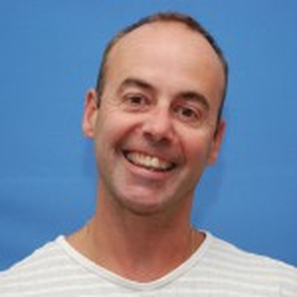 A headshot of William with a big smile in front of a blue background.