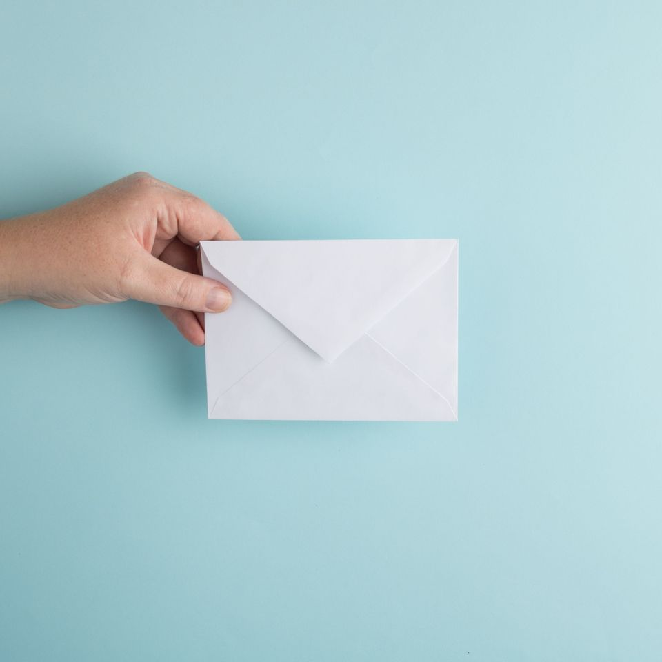 A picture of a white envelope being held in a hand against a light blue backdrop.