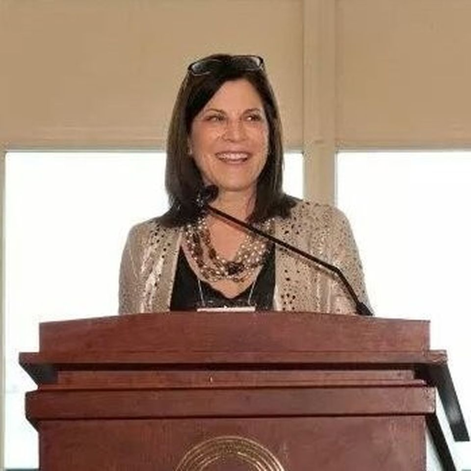 A picture of Jodi with a big bright smile behind a microphone at a wooden podium.