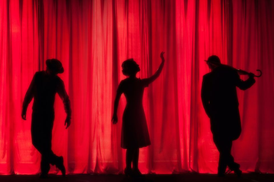 An image of three performers in silhouette against a red curtain.