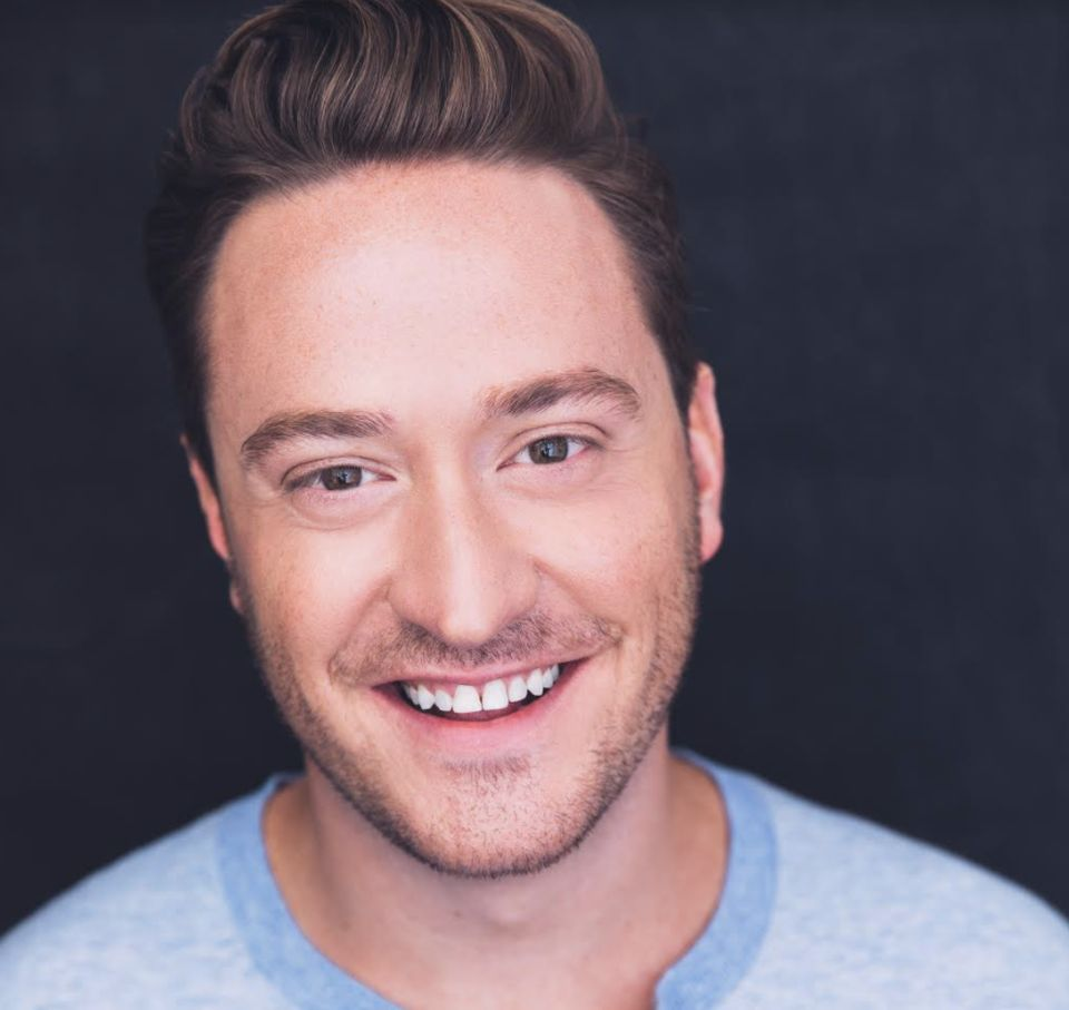 A headshot of Sean with a warm smile against a dark grey background.