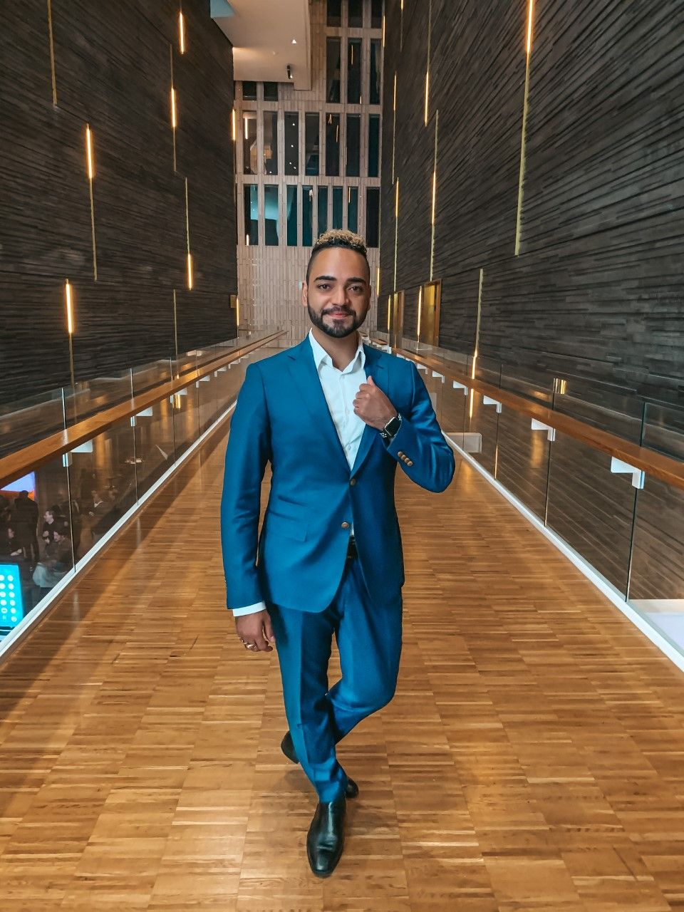 A picture of Mariano in a blue suit standing in a wooden-clad walkway.
