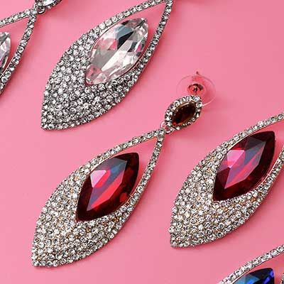 Diamond earrings displayed on a pink background