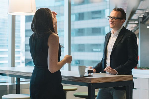 A business woman and man talking in an office kitchen