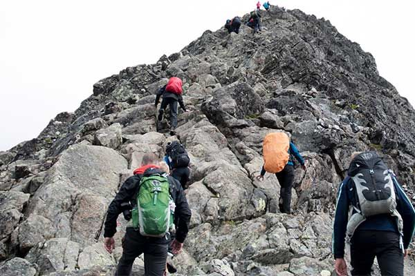 A team with rucksacks and climbing gear hiking up a mountain
