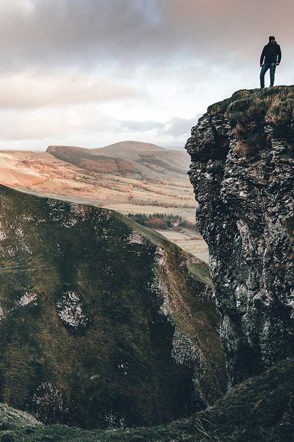 Man on top of a mountain looking at horizon