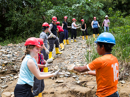 Young travellers passing rocks to each other in a line on a volunteer project in the rainforest