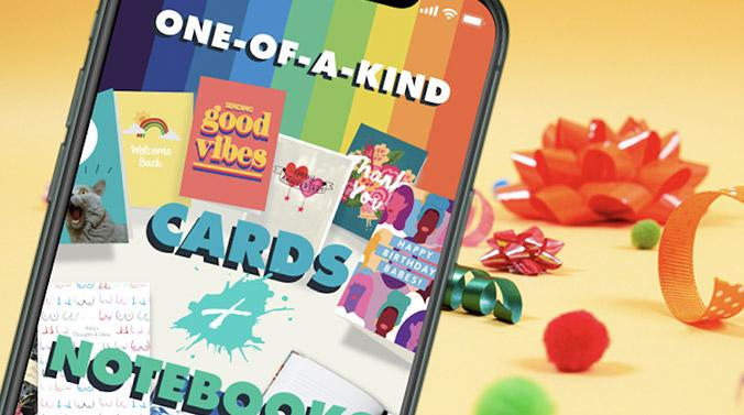 Bright orange background with gift bow and ribbons in the background with green and red pom poms. Phone with screenshot of the Paperchase Plus App home screen, rainbow stripe on featuring various cards and notebooks.