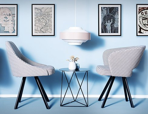 Upholstered chairs with individual fabrics in front of blue wall with pictures