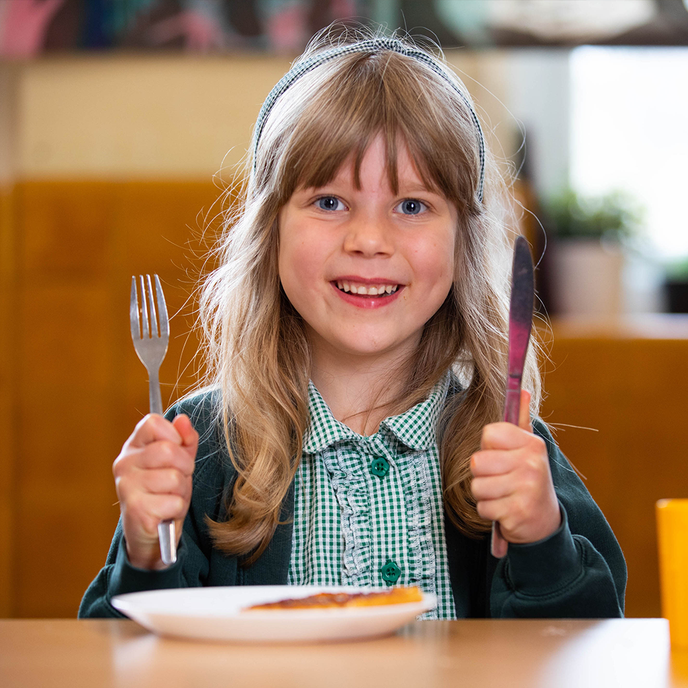 Young girl smiling with hand and fork in hand