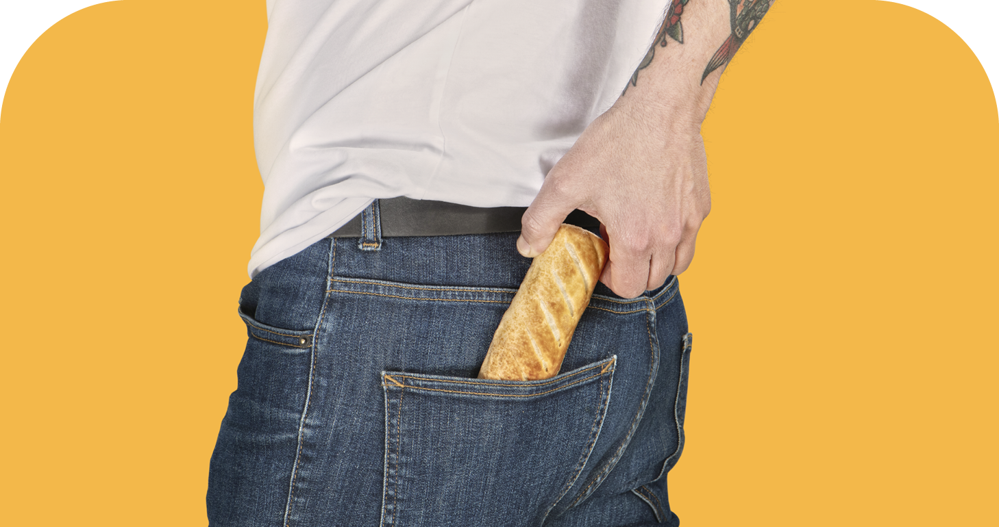 A man pulling a sausage roll from his back pocket