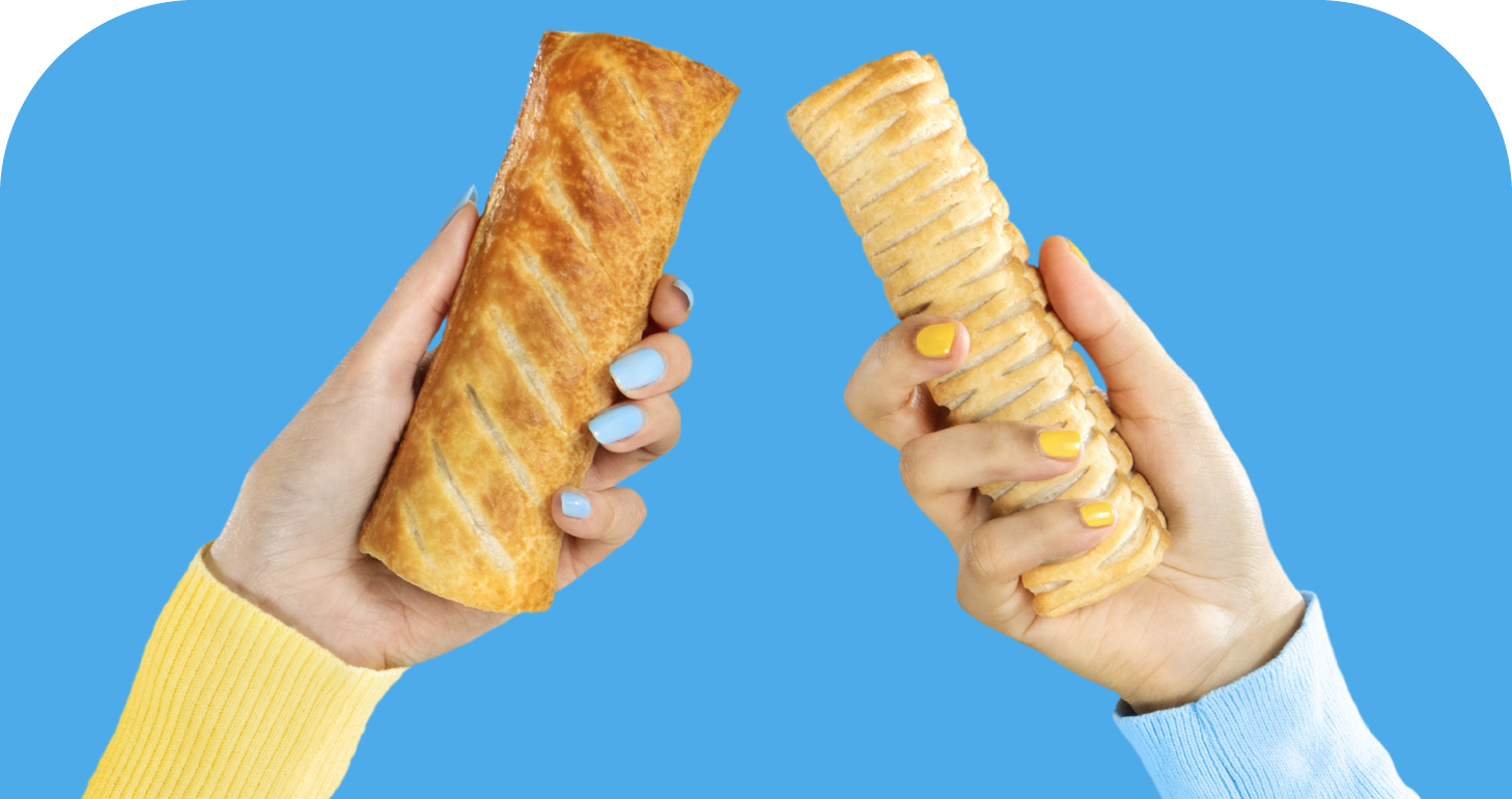 Two sausage rolls being held aloft