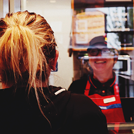 Shop worker behind social distancing screen